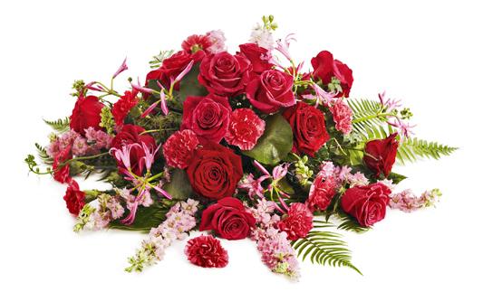 Låg blomdekoration med rosor, nejlikor och sommardelifinium.
