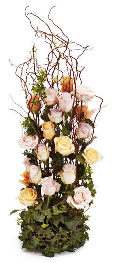 Högt blomsterarrangemang med rosor och grenar (höjd ca. 65 cm).