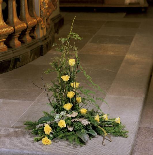 Bukett med material från skogen och gula rosor.