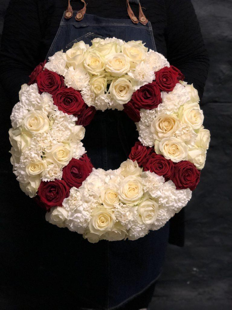 Ett blomsterbinderi I form av en livboj i vitt och rött.