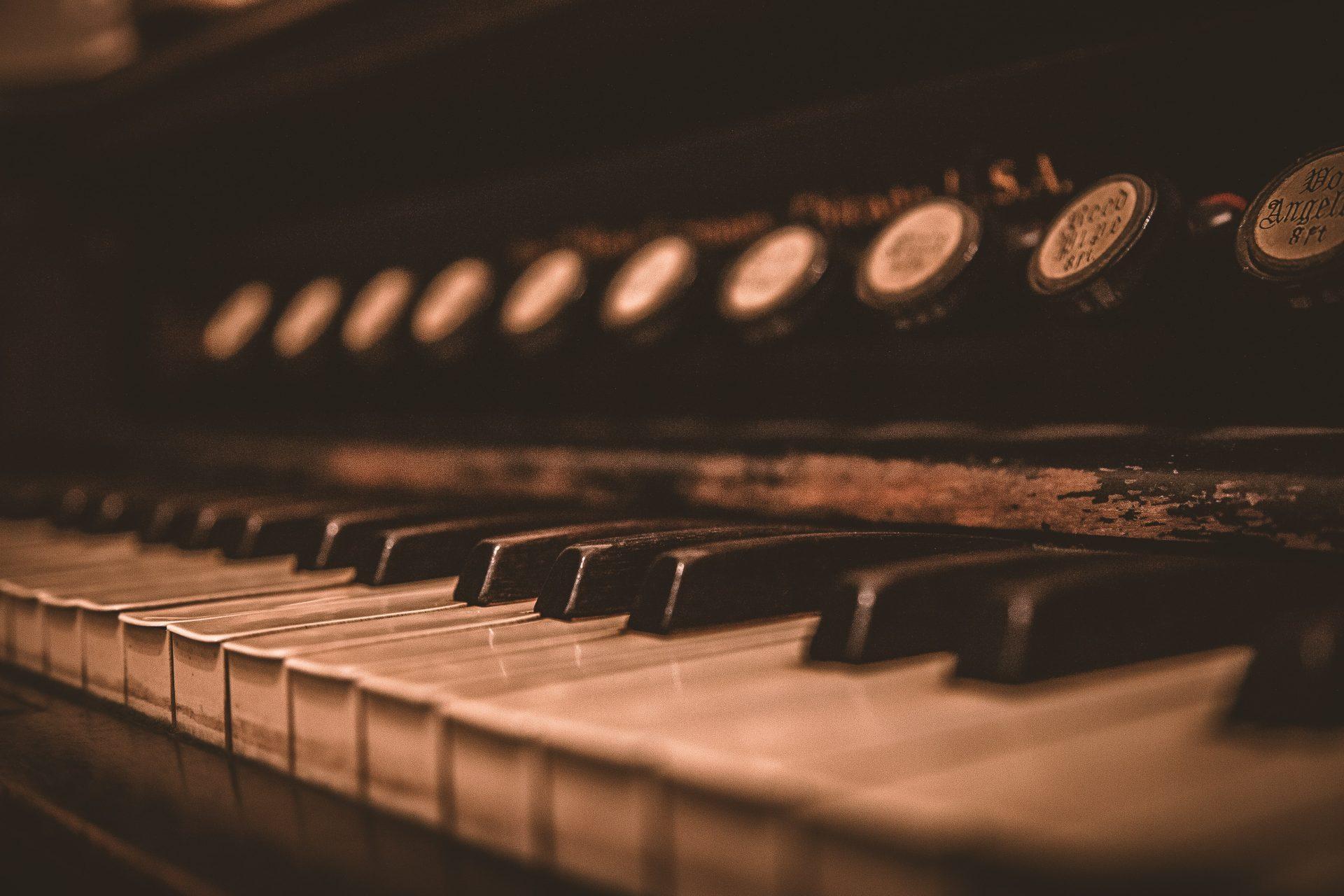 Bild på klaviatur och reglage tillhörande en äldre tramporgel.