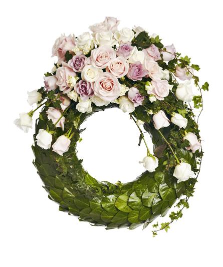 Blomkrans med blommor i ljusa toner av rosa och lila.