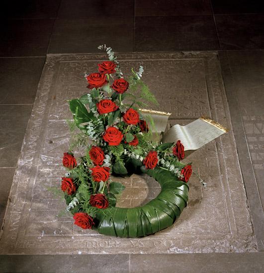 Blomkrans med röda blommor och band.